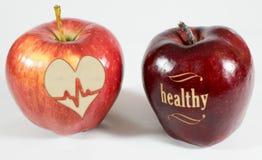 1 manzana con la inscripción sana y una manzana con un corazón Fotografía de archivo libre de regalías