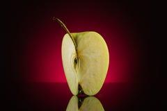 Manzana cuarta en fondo rojo oscuro Foto de archivo