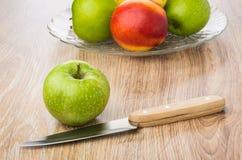 Manzana, cuchillo de cocina y plato verdes con las nectarinas, peras, appl Fotos de archivo libres de regalías
