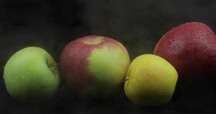 Manzana de la fruta tropical en nubes de hielo frías del humo de la niebla en fondo negro metrajes