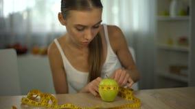 Manzana de medición de la muchacha anoréxica con la cinta, contando calorías y el índice de masa corporal metrajes