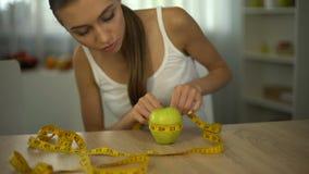 Manzana de medición de la muchacha con la línea de la cinta, contando calorías, el alimento biológico y la dieta metrajes