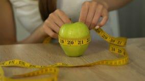 Manzana de medición de la mujer con la cinta-línea, calorías calculadoras, índice de masa corporal metrajes