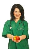 Manzana de ofrecimiento del ayudante de sanidad Imágenes de archivo libres de regalías