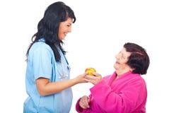 Manzana de ofrecimiento del doctor a un paciente mayor Imágenes de archivo libres de regalías