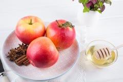 Manzana dulce orgánica fresca, madura en plato con los palillos de canela, estrellas del anís y miel Fotografía de archivo