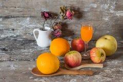 manzana en la naranja y la pera de madera, jugo de la cucharada en un vidrio Fotografía de archivo libre de regalías