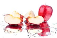 Manzana entera de las manzanas rojas y cutted en cierre aislado fondo blanco encima de la macro imagen de archivo libre de regalías