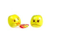 Manzana feliz y triste de los emoticons que lame una piruleta Sensaciones, actitudes y emociones imagenes de archivo