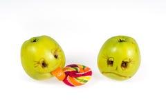 Manzana feliz y triste de los emoticons que lame una piruleta Sensaciones, actitudes y emociones Foto de archivo libre de regalías