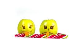 Manzana feliz y triste de los emoticons que lame una piruleta Sensaciones, actitudes y emociones Imagen de archivo libre de regalías