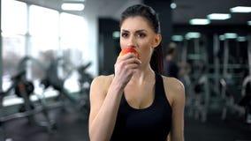 Manzana femenina de la consumición del deporte después del entrenamiento, nutrición equilibrada, forma de vida activa foto de archivo libre de regalías