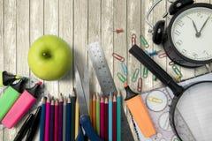 Manzana fresca con las fuentes de escuela en la tabla Fotografía de archivo libre de regalías
