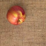 Manzana fresca en fondo de la textura de la materia textil de la arpillera Fotos de archivo libres de regalías