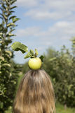 Manzana fresca encima del woman& rubio x27; cabeza de s Imágenes de archivo libres de regalías