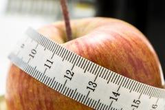 Manzana fresca envuelta en una cinta métrica Imágenes de archivo libres de regalías