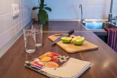 Manzana fresca y dos tazas de agua en encimera en kitche moderno Imágenes de archivo libres de regalías