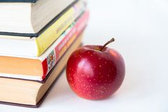 Manzana jugosa madura roja cerca de los libros imágenes de archivo libres de regalías