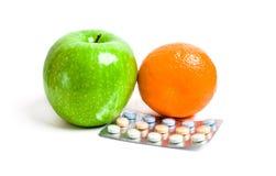 Manzana jugosa y vitaminas anaranjadas, verdes Fotografía de archivo