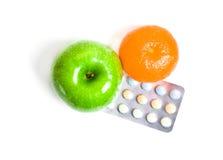 Manzana jugosa y vitaminas anaranjadas, verdes Imagen de archivo