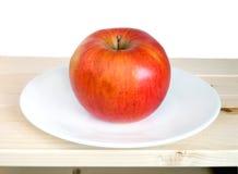 Manzana madura grande en el primer blanco de la placa Foto de archivo
