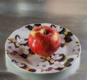 Manzana madura, roja en un platillo Foto de archivo libre de regalías