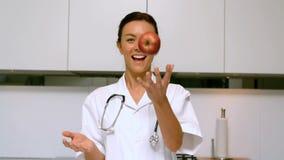Manzana que lanza y de cogida de la enfermera casera y que sonríe en cocina almacen de video