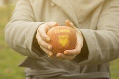 Manzana que se sostiene femenina irreconocible con te amo la impresión en Fotografía de archivo