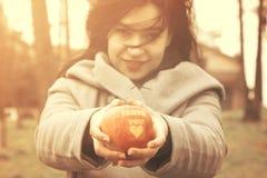 Manzana que se sostiene femenina joven con te amo la inscripción en el parque Imagen de archivo