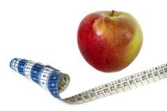 Manzana roja, cinta de la medida aislada en blanco Fotos de archivo
