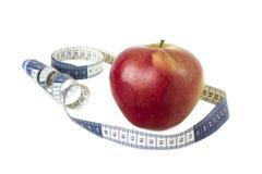 Manzana roja, cinta de la medida aislada en blanco Imágenes de archivo libres de regalías
