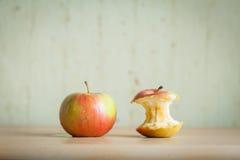 Manzana roja con el tocón en el tablero Imagen de archivo