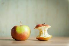 Manzana roja con el tocón en el tablero Foto de archivo libre de regalías