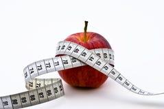 Manzana roja con la cinta de medición Imagen de archivo libre de regalías