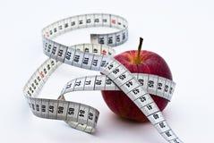 Manzana roja con la cinta de medición Foto de archivo libre de regalías