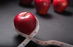 Manzana roja con la cinta de medición Imágenes de archivo libres de regalías