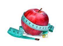 Manzana roja con la cinta métrica aislada en blanco Imagen de archivo