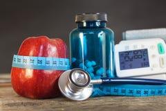 Manzana roja con la cinta métrica para medir longitud Tratamiento de la obesidad y diabetes, medida de la presión arterial Imagen de archivo