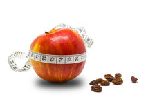 Manzana roja con la cinta métrica y las pasas Imagenes de archivo