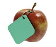 Manzana roja con la etiqueta verde imagen de archivo