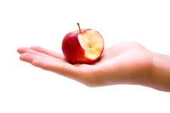 Manzana roja con una mordedura que falta en la mano Imágenes de archivo libres de regalías