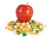 Manzana roja contra píldoras fotografía de archivo