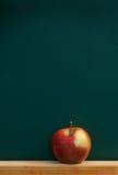 Manzana roja en la pizarra Fotos de archivo