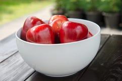 Manzana roja en la taza blanca Fotos de archivo libres de regalías
