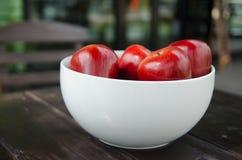 Manzana roja en la taza blanca Foto de archivo libre de regalías