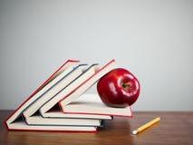 Manzana roja en los libros Foto de archivo