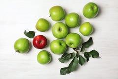 Manzana roja entre verde unos en el fondo de madera, visión superior foto de archivo libre de regalías