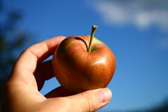 Manzana roja fresca a disposición con el cielo azul en fondo Foto de archivo