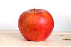 Manzana roja madura grande en primer de madera beige del estante Foto de archivo libre de regalías