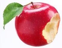 Manzana roja mordida con una hoja Fotos de archivo